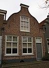 foto van Huis onder zadeldak en met ingezwenkte halsgevel