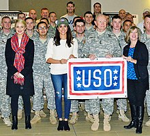 Dianna Agron and Meghan Markle, dressed casually and surrounded by military service personnel, hold a USO banner.