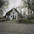 Gezicht op stolpboerderij met klokgevel met hoekvoluten bij het voorhuis vanaf de weg - Twisk - 20406598 - RCE.jpg