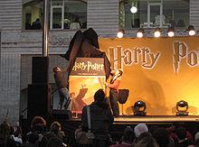 Deux hommes retirant un drap noir d'une couverture de livre géante, dans les tons orange et noir, montrant Harry la main levée et lançant un sortilège