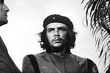 "Black-and-white image of a man looking to his right. He wears a black beret with a little ""x"" and a closed jacket. His hair is shoulder-length, curly and black. On his right there is a man looking to him and on his left, there is a plant."