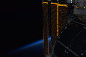 Electrical system of the International Space Station - An ISS solar panel intersecting Earth's horizon.
