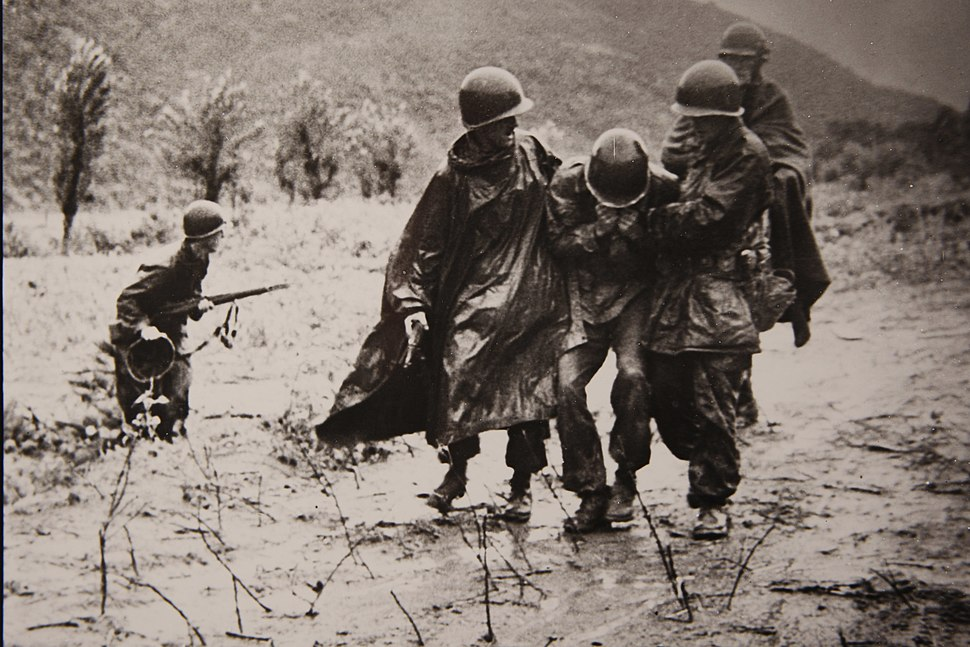 In this undated file photo, U.S. Army Capt. Emil Kapaun, right, a chaplain with the 3rd Battalion, 8th Cavalry Regiment, 1st Cavalry Division, helps a Soldier carry an exhausted troop off the battlefield 130311-A-CP123-001