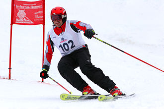 Carved turn - This skier is in the middle of a high-performance turn during a slalom race. The arced shape of the ski can be seen, especially on the outside ski (right side of the image).