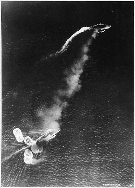 Japanese aerial photo of the initial attack on Prince of Wales (top) and Repulse. A short, thick plume of black smoke can be seen emanating from Repulse, which has just been hit by a bomb and surrounded by at least six near misses. Prince of Wales can be seen to be manoeuvring. The white smoke is from the funnels as the ships attempt to increase speed. Japanese high-level bombing attack on HMS Prince of Wales and HMS Repulse 1941-12-10.jpg
