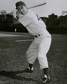 A man in a white baseball uniform holding his bat behind his head prepares to swing.
