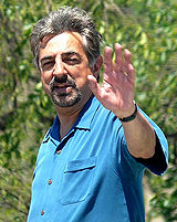 Colored photograph of a man, waving with his left arm. He is wearing a blue shirt.