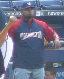 A bearded, dark-skinned man in a red-and-navy blue jacket and gray baseball pants throwing a baseball with his right hand