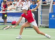 Justine Henin performing a backhand volley.