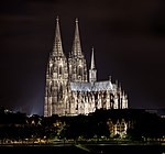A large, brightly lit cathedral sits in the middle of a skyline at night.