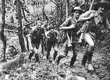 Soldiers in short sleeve shirts and shorts, slouch hats and helmets march up a muddy track carrying rifles slung over their shoulders