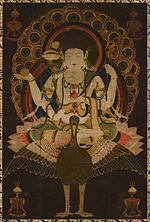 Frontal view of a deity with four arms seated on a bird in lotus position embellished with ornaments.