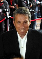Photograph of director Ivan Reitman at a red carpet event with photographers behind him