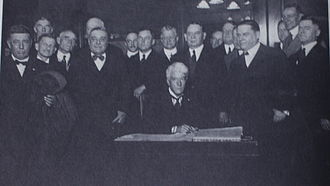 Kenesaw Mountain Landis - Landis, surrounded by baseball owners and officials, signs an agreement to be Commissioner of Baseball, November 12, 1920.