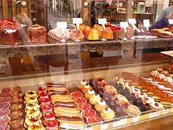 Shop display featuring multiple rows of small, colourful pastries.