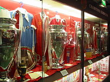 Four trophies inside a glass cabinet. The trophies have ribbons on them and there is memorabilia next to them