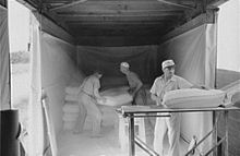 three people loading dusty flour in bags into a boxcar, interior view