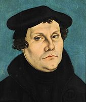 Portrait of Luther by the painter Lucas Cranach the Elder, showing the face in detail, while hair, jacket and a barett are black and frame it