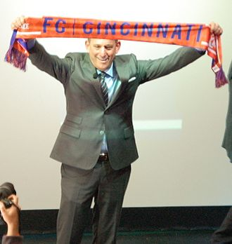 FC Cincinnati - Don Garber raises an FC Cincinnati scarf during his 2016 town hall meeting.