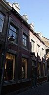 foto van Hoekhuis met brede lijstgevel met een gevelsteen met koetspoort 17 IN:DE:RODE:POORT:39.