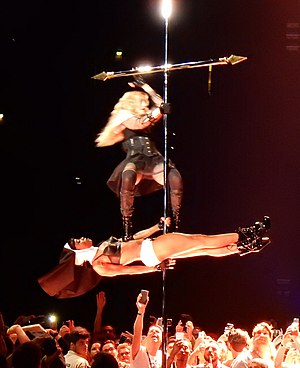 "Rebel Heart Tour - The Rebel Heart Tour consisted of many intricate choreographies. On the picture, Madonna performing ""Holy Water"" while gyrating around a cross, standing on a dancer dressed as a nun."