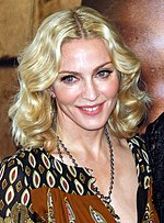 1/4 length image of Madonna. She is wearing a blouse and necklace. Her hair is wavy.