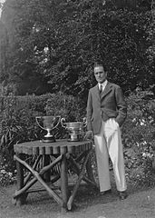 Man standing next to a garden table on which are golfing trophies