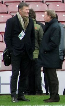Two men wearing mostly dark coloured clothing stand at the side of a football pitch, hands in pockets, staring past end other.