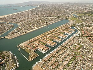 Long Beach Marine Stadium - Aerial view of Marine Stadium in Long Beach, California, looking southwest, with the Belmont Shore neighborhood and beach visible in the near distance, the downtown Long Beach skyline in the middle distance, and the Palos Verdes Peninsula in the background.