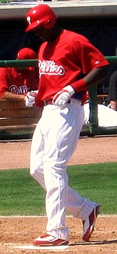 A dark-skinned man in a red baseball jersey, white baseball pants with red pinstripes, and a red batting helmet steps on home plate with his left foot while looking down.