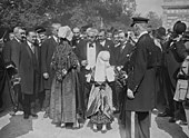Besnorde man met grijs haar die wisselt met een vrouw en een meisje gekleed in traditionele outfits;  op de achtergrond zijn andere mannen