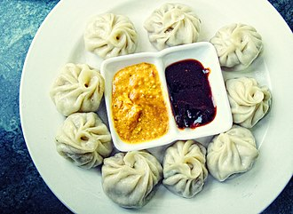 Momo (food) - A typical serving of a plate of momo with sesame yellow and red garlic chilli sauce.