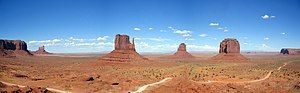 Monument Valley - Panorama taken from the Visitor Center, showing the West and East Mitten Buttes and the road making a loop-tour through the Park