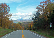 A two-lane highway in a wooded area during autumn. It drops away in the center, with a view toward a distant landscape with a body of water and mountains beyond. On the right is a sign with the number 22