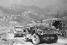 Reconnaissance car going uphill, followed by another car