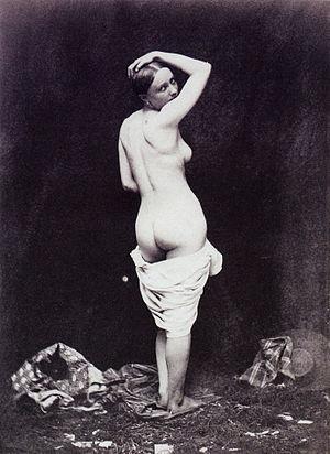 Français : Femme nue debout, vêtements épars P...
