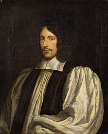 A middle-aged white man seated and dressed in clerical robes.
