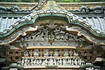 White carved figures under an undulating gable.