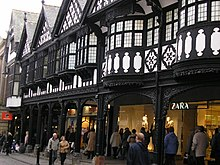Part of a range of gabled shops seen from ground level. The lower storey contains modern shop fronts behind an arcade, The upper storey is timber-framed and contains bow windows in the foreground and oriel windows beyond.