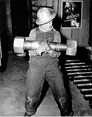 One-hundred, ninety-three pound nut and bolt, one of 16 used to join sections of the generator shaft of a 75,000 kW generator - Grand Coulee Dam, 1942.jpg