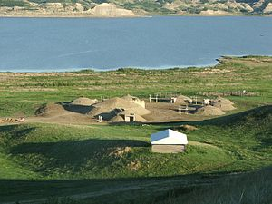 Distant overhead view of circle of reconstructed earth lodges, with lake in background