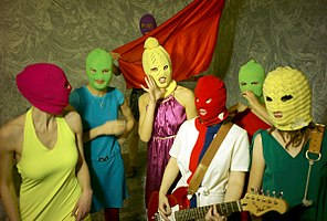 7 women with bright colored clothes and multicolored knit ski masks over their faces. A woman at the center holds a guitar and one at the back holds a piece of red fabric.