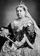 Fotografie alb-negru a reginei Victoria purtând un voal de dantelă acoperit cu o coroană mică, are în mână un ventilator închis.