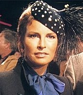 Welch in blue scarf and high-collared gray jacket, with polka-dot feathered cap