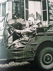 Assise au volant d'une Jeep, la reine vêtue d'un manteau en cuir et coiffée d'un casque se trouve devant un officier souriant et portant un képi et d'une dame coiffée d'un chapeau-cloche
