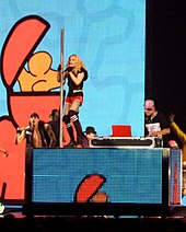 A blond woman stands atop a rectangular black box. She wears red shorts and sings into a microphone, while holding a pole atop the box, with her right hand. A man is seen beside her, wearing a cap. The backdrop behind them display light blue patterns.