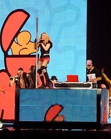 A middle aged blond woman dancing on a DJ's desk wearing red shorts and a black sleeveless shirt. She's holding on to a pole with her left hand and holds a microphone to her mouth with her right hand. She is flanked by dancers