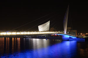 MediaCityUK - The MediaCityUK footbridge at Salford Quays illuminated at night. The Imperial War Museum North is seen in the background.