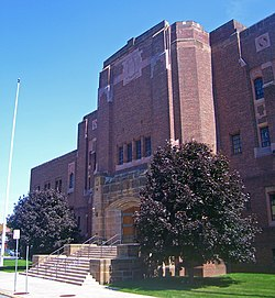 Front view of entrance and north wing of armory, a brown brick building in the Art Deco architectural style