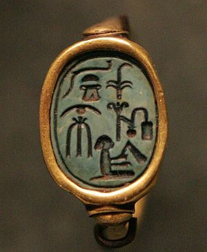 """Scribe equipment (hieroglyph) - Seal ring. (Note also, hieroglyphs: bread bun (T), and jar stand (G). Starting with 'sedge'-(""""king""""), Column 2-(on right):  """"(The) King's Scribe"""",  Column 1-(left): """"Overseer of the Harem, AhMose"""".  the central figure: """"seated man with flail"""", is a determinative for """"(seated)-Man-noble"""".) (i.e. """"Ah-Mes, (The)-Noble Man"""")"""